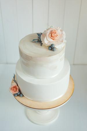 Laconic white wedding cake decorated with sugar flowers Reklamní fotografie - 100931626