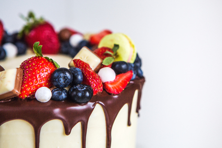 Beautiful cream colored cake decorated with strawberries, blueberries, chocolate, macaroon, standing on white wooden table on a high pedestal. 免版税图像