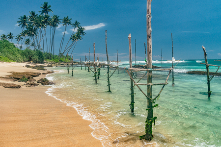 Sunny beach near Koggala - Sri Lanka The area famous for its distinct stilt fishermen, who erect a single pole in the chest-deep water on the beach, just few meters off-shore. Splittoned, vivid image.