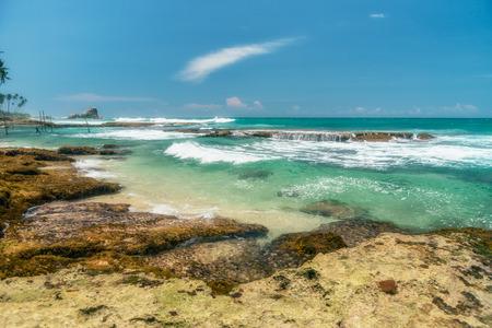 distinct: Sunny beach near Koggala - Sri Lanka The area famous for its distinct stilt fishermen, who erect a single pole in the chest-deep water on the beach, just few meters off-shore. Splittoned, vivid image.