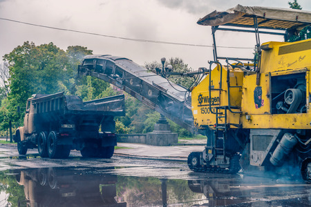 MIRGOROD, UKRAINE : Workers and machines repairs the road. This is standard procedure in Ukraine after winter. Stock Photo