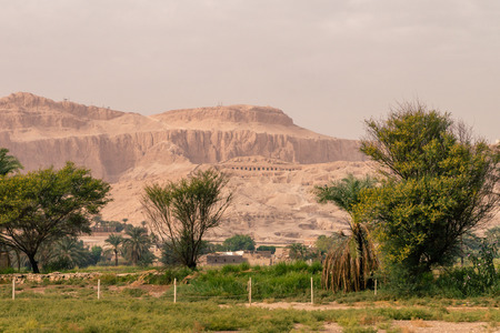 LUXOR, EGYPT: Ancient Colossi of Memnon in Egypt at noon. The original function of the Colossi was to stand guard at the entrance to Amenhoteps memorial temple. Editorial