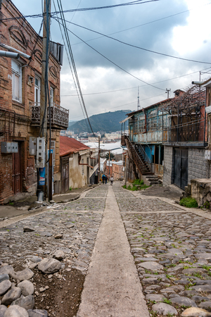 cooper: TBILISI, GEORGIA - APRIL 04, 2017: Street of old city, Tbilisi at the spring. Historically Tbilisi has been home to people of multiple cultural, ethnic, and religious backgrounds. Editorial
