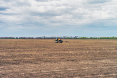 Tractor preparing the field before seeding the ground. Wheat - main crops, which are grown in Ukraine Stock Photo