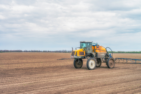 Tractor preparing the field before seeding the ground in Ukraine