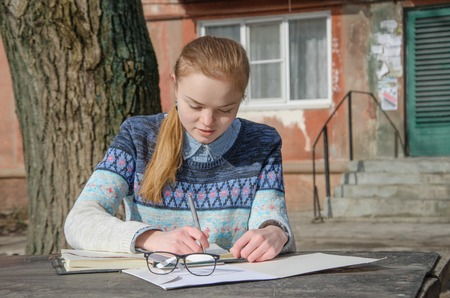 carroty: carroty girl student writing homework outdoor the sunlight Stock Photo