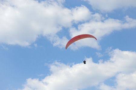 paraglide: Silhouette of paraglide flying in the sky with clouds in a light of sunrise. Ukrainian Carpathian valley.