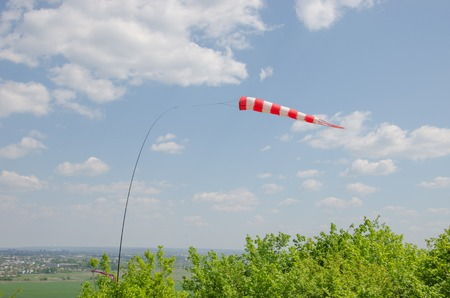 wind force: Air field direction sign and a wind force windsock against the  blue sky with clouds. Stock Photo