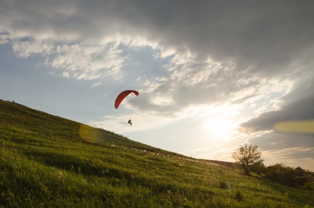 paraglide: Silhouette of paraglide flying in the sky with clouds in a light of sunrise. Ukrainian Carpathian valley