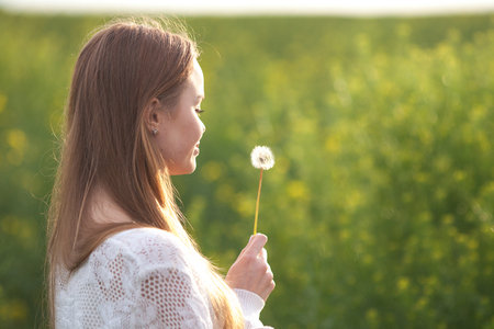 blowing dandelion: Young spring fashion woman blowing dandelion in spring garden. Springtime. Stock Photo