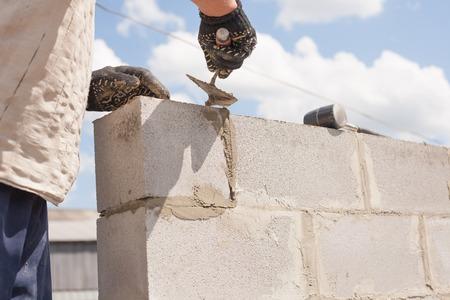 작업자는 주걱으로 정렬, 벽돌 콘크리트 블록을 배치합니다. 스톡 콘텐츠