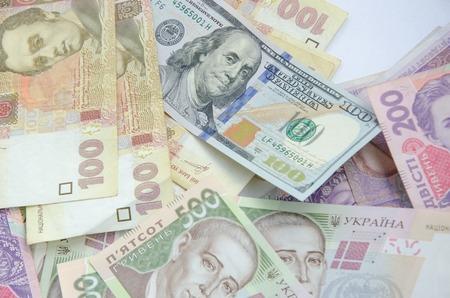 one hundred dollar bill: One hundred dollar bill on the background of ukrainian hryvnia