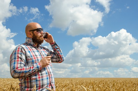 hairless: hairless farmer in glasses standing in a wheat field and talking on phone