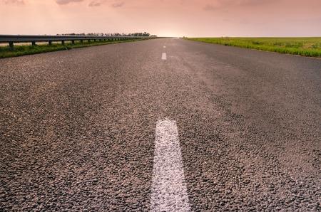 yellow line: Empty asphalt road to pink beautiful sunset Stock Photo