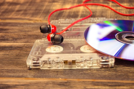 black rapper: Retro compact cassette with disc and headphones on wood Stock Photo
