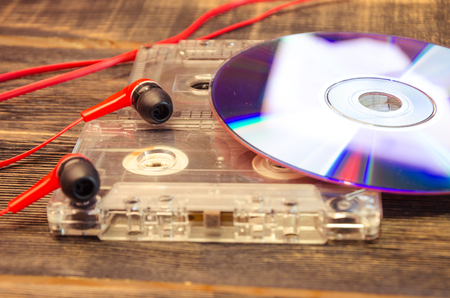 Retro compact cassette with disc and headphones on wood Stock Photo