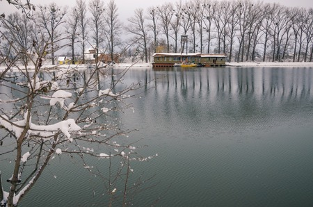 adds: A boat encased in ice on a lake in winter. Above the boat is a big oak tree with a bench. The fog at sunset adds to the mystery of the scene.