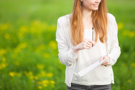 carroty: Young freckled girl agronomist or biologist in white blouse standing in green field with notebook and pen during harvest Stock Photo