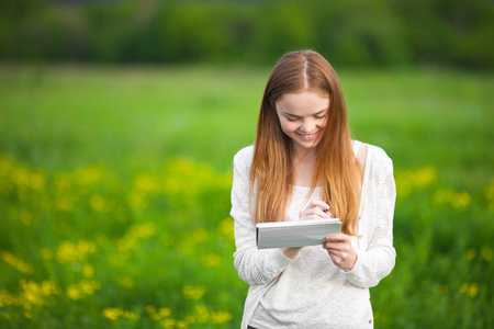 Young freckled girl agronomist or biologist in white blouse standing in green field with notebook and pen during harvest Stock Photo