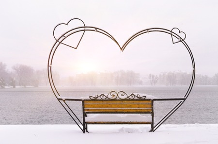 snowcovered: empty snow-covered wrought-iron bench in the form of hearts for couple of lovers in winter park