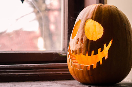 windows and doors: Creepy halloween scary pumpkin with a smile at the old wooden background doors.