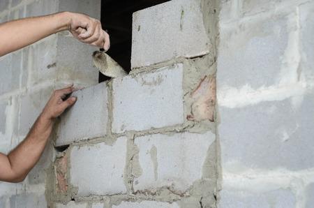 Migrant worker building cinder block wall in desert setting Stock Photo