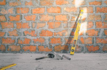 Mason bricklaying background with level, hammer and clay brick blocks