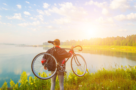 man stand with bicycle in hands on the hill and looking at the lake with azure water and sunrise Stock Photo