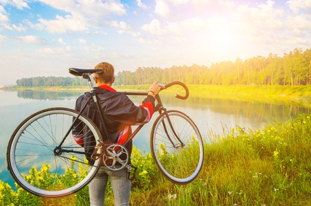man stand with bicycle in hands on the hill and looking at the lake with azure water and sunrise Banco de Imagens