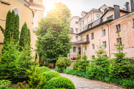 Path crossing flowered yard with people and old building in the Garden of Plants in Paris. Stock Photo