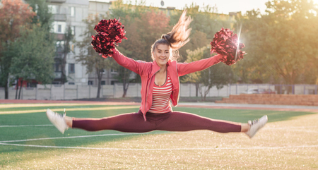 Girl in pink sport suit with pompoms doing splits at the stadium Stock Photo