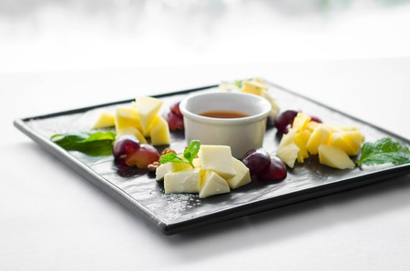 Assorted cheeses with honey and nuts in the black plate in restaurant.