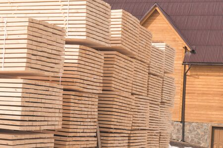 stack of wooden material for building. new big wooden house Фото со стока