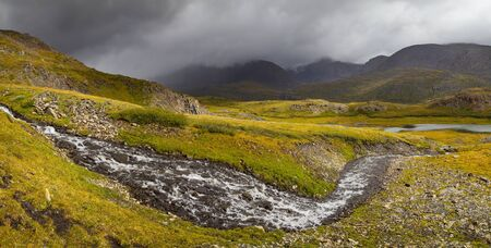 Wild place in the mountains of Altai. A rough river flows among the mountain tundra. Gloomy sky and light in the valley.
