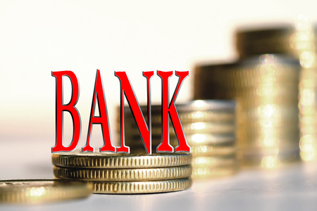 monies: The word Bank in the background the columns of coins. The concept of financial instability on the market.