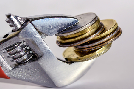 robustness: Wrenche and coin. The concept of financial reliability. Stock Photo