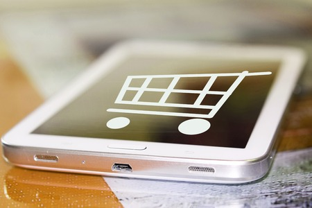 The shopping cart on the cell phone screen. The concept of online trading and online stores. Stock Photo
