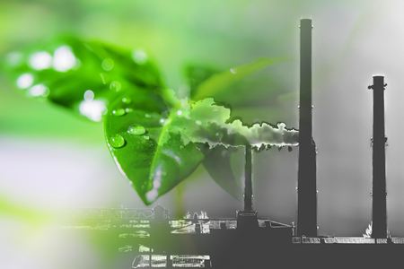 Industrial factory chimneys on background of green plants. The concept of relevance for the protection of nature