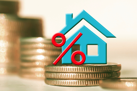 The percent symbol and real estate on a background of money. The concept of price changes on the real estate market Stock Photo