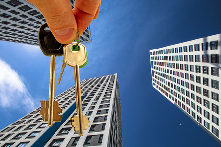 premises: The keys to the apartment in the background of the facade of the house. The concept of sales in the real estate market. Stock Photo
