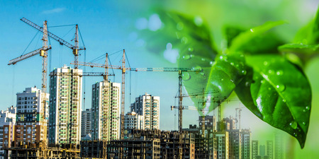 The construction of new tall buildings on a background of green plants. The concept of environmental clean construction. Stock Photo