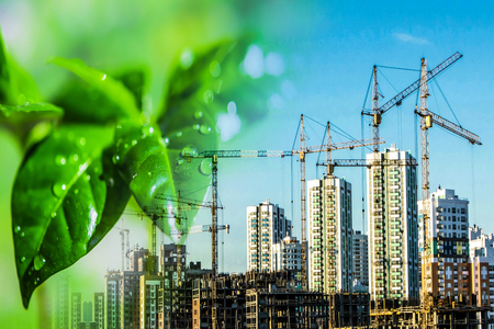 The construction of new tall buildings on a background of green plants. The concept of environmental clean construction. Stok Fotoğraf