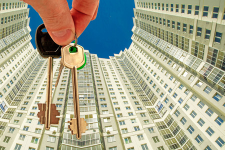 The keys to the apartment in the background of the facade of the house. The concept of sales in the real estate market. Stock Photo