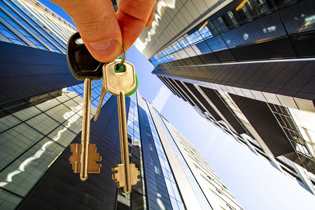 The keys to the apartment in the background of the facade of the house. The concept of sales in the real estate market. Stok Fotoğraf