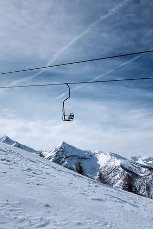 Siluette of a single chair lift hanged over fresh snow and blue sky