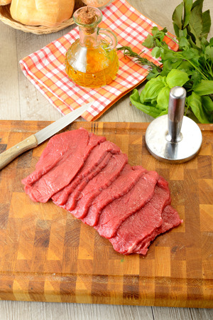 slices of raw meat on cutting boarb photo