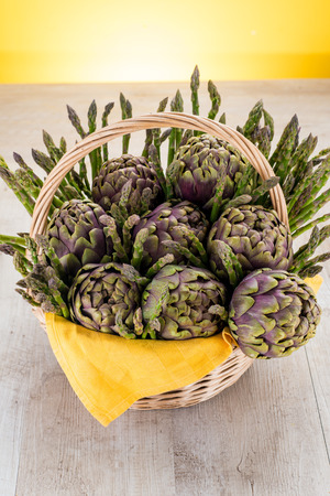 cardunculus scolymus: Basket with artichokes and asparagus Stock Photo