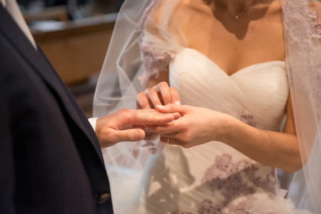 Bride puts the ring on groom\ photo