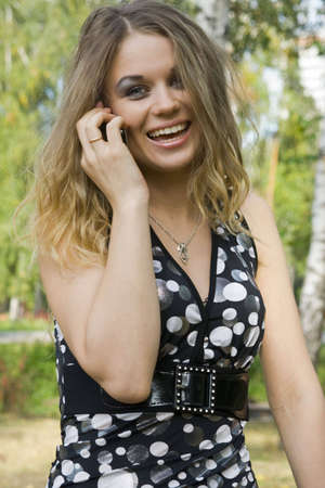 listened: young woman blonde on a background trees in a park.Model Valentina Larkina Stock Photo