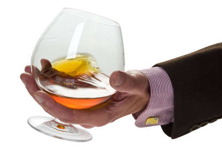 Glass with cognac in a palm of the man on a light background Stok Fotoğraf